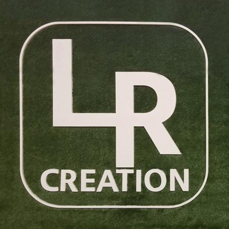 Enseigne Logo LR Création en PVC expansé 19 mm blanc, sur un fond d'herbe synthétique, une imitation parfaite d'un gazon naturel